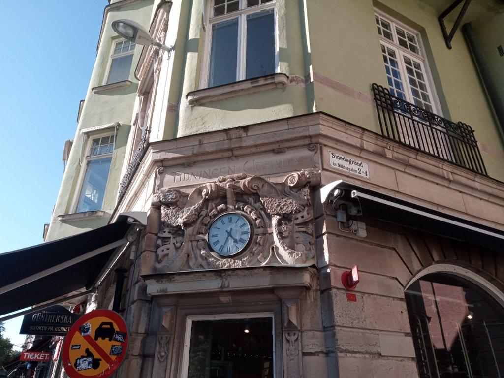 Fasad med en klocka och texten Tidningen Uppsala inhuggen i fasaden.